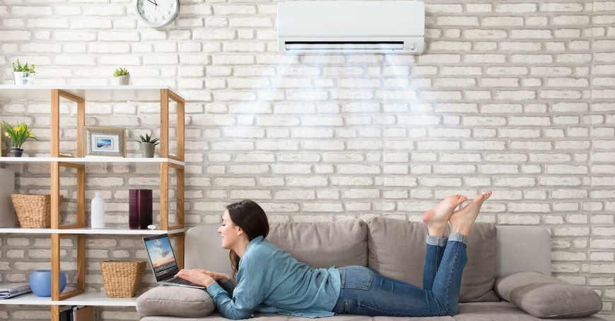 Djevojka s laptopom leži na dvosjedu ispod klima uređaja ugrađenog na zid od bijele cigle